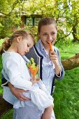A woman with a little girl eating vegetable crudites in a garden