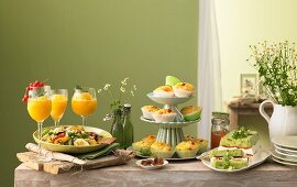 Summer buffet with various dishes, a bunch of flowers and drinks