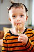 A little boy eating a jelly snake