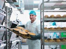 Bäcker holt frisch gebackene Kuchen aus dem Ofen in einer Kuchenfabrik