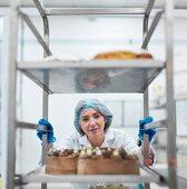 Bäckerin schiebt Rollwagen mit frisch gebackenen Kuchen in der Kuchenfabrik