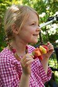 A little girl in a garden holding a fruit skewer