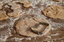 Boot-shaped shortbread biscuits being cut out on a floured work surface