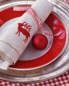 Rot-weisses Karoband mit Weihnachtskugel um bestickte Leinenserviette mit Hirschmotiv