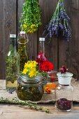 Verschiedene selbstgemachte Öle dahinter zum Trocknen aufgehängte Kräuter