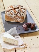 A square loaf of rye bread and dates on a ceramic platter with a slice of cheese next to it
