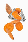 A grater with a sweet potato and sweet potato slices