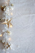 A string of fairy lights with origami stars and origami fir trees