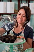 A woman lifting a glass cloche from chocolate muffins on a cake stand