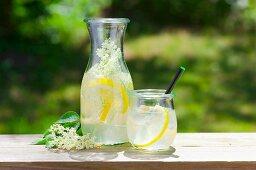 Lemonade with elderflowers on a table outside