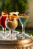 Blueberry, granadilla and papaya lassis garnished with almonds and slices of fruit