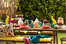 Colourful, set table with lanterns, animal figurines, yellow seat cushions on bench and ethnic scatter cushions
