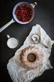 A Bundt cake dusted with icing sugar on a piece of white paper with redcurrants in a vintage sieve on a grey slate surface