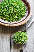 Organic split peas on a spoon and in bowl on a wooden surface