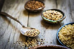 Brown rice, quinoa and buckwheat on a wooden surface