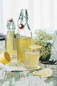 Bottles of elderflower syrup and a glass of elderflower cordial with a slice of lemon