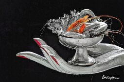 Silberhand hält Schale mit versilberten Garnelen