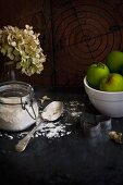 An autumnal arrangement with green apples, flour and cutters