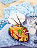 Pasta salad with chicken, pepper and spinach for a beach picnic
