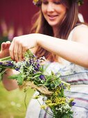 Woman tying wreath of flowers for midsummer festival
