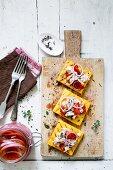 Polenta-Crostini mit eingelegten roten Zwiebeln und Fisch