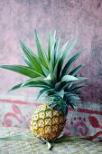 A fresh pineapple against a wall
