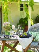Garden table set with white wine and fruit