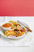 A salad featuring grilled pineapple and mango with a masala dressing