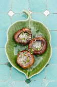 Grilled mushrooms with herb butter on a leaf-shaped plate