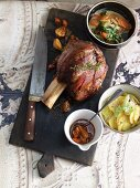 Veal knuckle with potato salad and summer vegetables