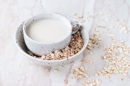 A cup of oat milk in bowl of oats on a marble surface