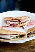 Ham on unleavened bread wrapped in paper on a plate
