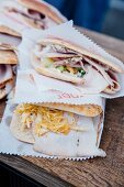 Various flatbread sandwiches wrapped in paper