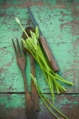Wild asparagus on a rustic wooden table with salad servers and a knife