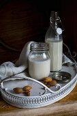 Veganer Mandeldrink in Bügelflasche & Schraubglas auf Tablett