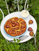 Fig tarte tatin with vanilla sauce on a garden chair