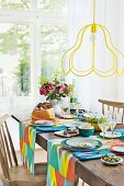 A table laid with colourful accessories, sausage, cheese and bread