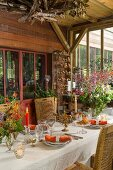 Autumnal dining table in conservatory with board wall