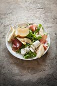 Salad with a roll of goats cheese roll, pears, Parma ham and pine nuts