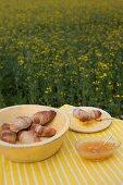 Croissants und Marmelade auf Tisch im Rapsfeld