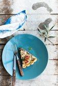 Ein Stück Tomatentarte mit Spinat und Feta auf blauem Teller