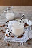 Almond milk in glass with a black and white striped straw, a jug of milk and scattered almonds