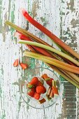 Pieces of rhubarb and strawberries in a glass bowl on a wooden table