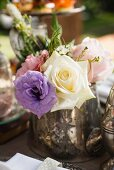 Silver vase of roses on tea-time buffet