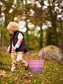 Little boy walking through an autumn woodland clearing