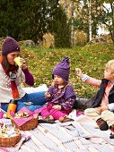 Mother and children enjoying an autumn woodland picnic