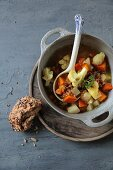 Vegetable stew with unripe spelt grains and a bread roll