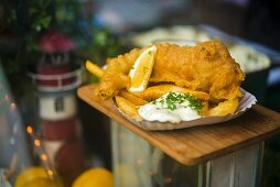 Fish and chips with remoulade in a paper dish