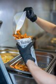 Sweet potato chips being transferred into a newspaper cone