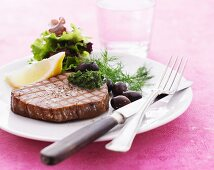Grilled tuna steak with dill pesto, olives and a side salad